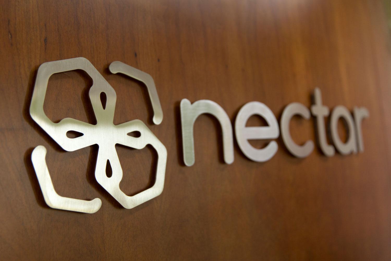 Nectat logo on wooden wall